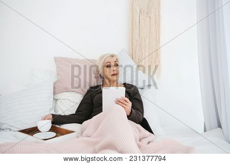 An Elderly Woman Lying In Bed Drinking Morning Coffee Uses A Tablet To View News Or Chat With Friend