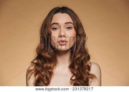Beauty portrait of a sensual young topless woman with brown curly hair looking at camera isolated over beige background