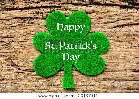 Happy St Patricks Day Message With Green Clover Leaf On Wooden Background