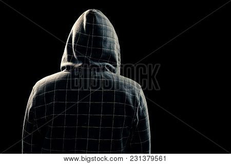 Portrait, Silhouette Of A Man In A Hood On A Black Background, His Face Is Not Visible. The Concept