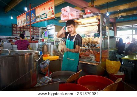 kuching,sarawak,malaysia 9th feb 2017,food court at kuching, sarawak. chef holding and showing his famous steam chicken