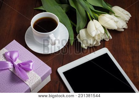 White Tulips, A Cup Of Coffee And A Gift On A Dark Wooden Background. Concept Of Spring.