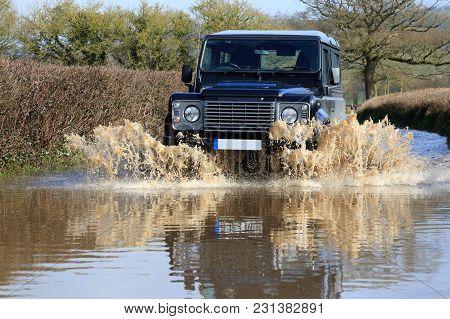Car Driving Through A Flooded Road In East Devon