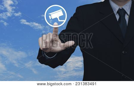 Businessman Pressing Cctv Camera Icon Over Blue Sky With White Clouds, Business Security Concept