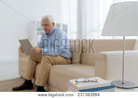 Stack Of Books And Glasses On Table In Room Of Reading Senior Man