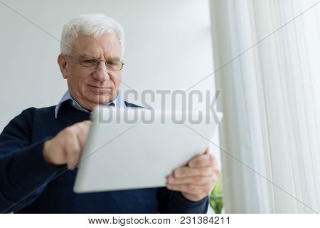 Senior Man In Glasses Learning How To Use Tablet Computer