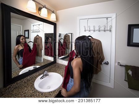 Black Female Deciding Between Dresses And Thinking About Choosing A Stylish Fashion To Wear.  She Is