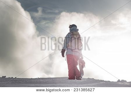 Snowboarder Girl Standing Hold Snowboard In The Clouds And Sun