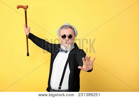 Happy senior man in hipster outfit on color background