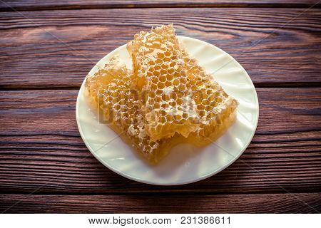 Honey In Honeycombs On A White Plate