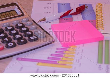 Business Accessories ( Notebook, Calculator, Fountain Pen) And Graphics, Tables, Charts On A Wooden