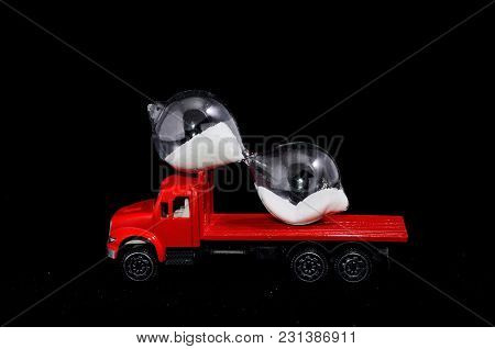 Time Transportation Concept Hourglass Watch On A Red Toy Truck Over Black Background
