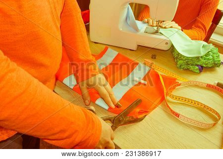 Fashion Designer, Woman Tailor Posing At Her Workplace With Cut Fabric, Free Space On Wooden Wall. G