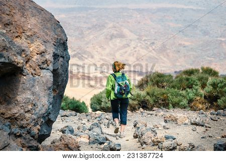 A Young Woman Is Walking In The Mountains And Admires Beautiful Views