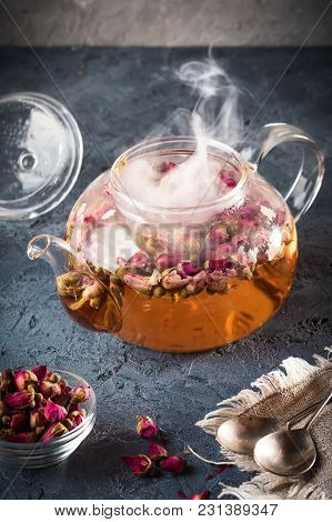 Teapot With Detox Drink From Flower Buds Dry Red Pink Rose Tea  Hot Water Steam On A Gray Stone Back