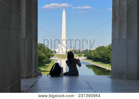 A tourist silhouette at the steps of Lincoln Memorial with Washington Monument and Capitol background - Washington DC USA