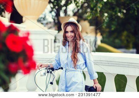 Vacation In The City. Young Woman Standing With A Bicycle In The Hat