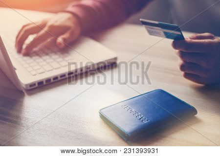 Man Holding Bank Card. Laptop And Passport On The Table. Web Shopping, Intentional Sun Glare And Len