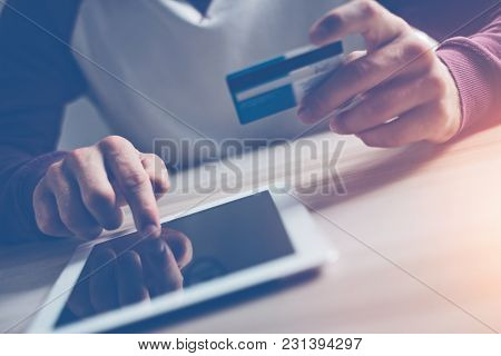 Man With Credit Card Making Internet Shopping Using Tablet Pc, Intentional Sun Glare