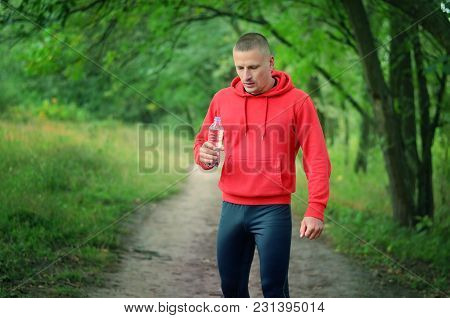 Runner In A Red Jacket With A Hood And Black Sport Leggins Hold In The Hand  Bottle With Water