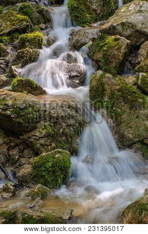A View Of The Mountain Stream Flowing In Cool Streams Along The Rocks Among The Green Grass And Flow