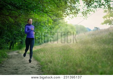 Young Slim Runner  In A Black Sports Leggins And And Blue Jacket  Fast Runs Along The Path  On The
