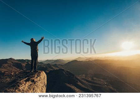 Man Stands Facing Rising Sun With Lift Up His Arms On Mount Sinai In Egypt.
