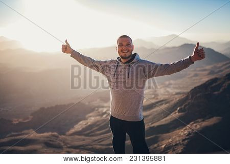 Happy And Joyful Man Stands Against Background Of Sunrise In Sinai Mountains At Egypt.