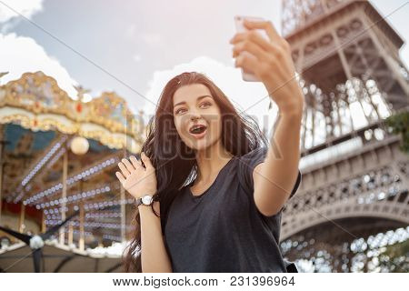 Happy Travel Woman Taking Funny Selfie With Her Mobile Phone Near The Eiffel Tower And Carousel, Par