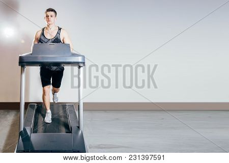 Handsome Man Doing Cardio Exercises, Running On Treadmills In The Gym.