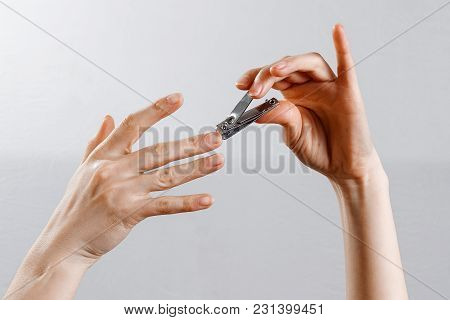 Female Hands Cut Off Nails On A White Background, Isolate.