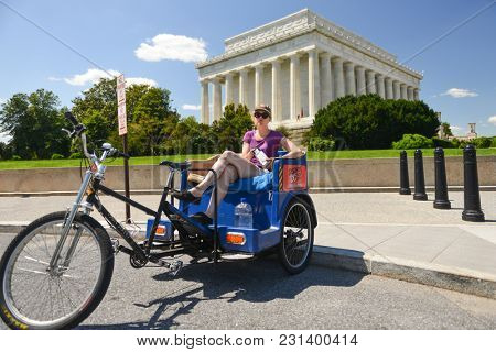 WASHINGTON DC / UNITED STATES - JUNE 01 2014: A pedicab sightseeing tour operator with Lincoln Memorial background - Washington DC United States