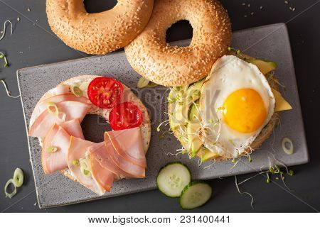 sandwiches on bagels with egg, avocado, soft cheese, alfalfa sprouts, ham, tomato