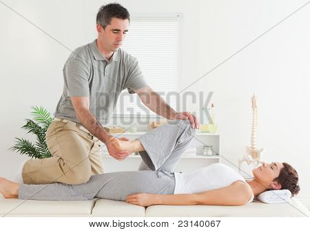 Chiropractor Stretching Young Woman's Leg