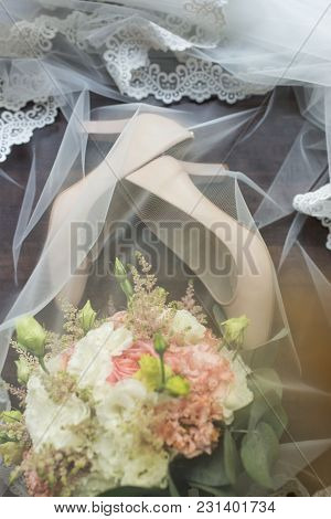 Beige Bridal Stylish Shoes And A Bouquet Covered With A Veil. Wedding Details.