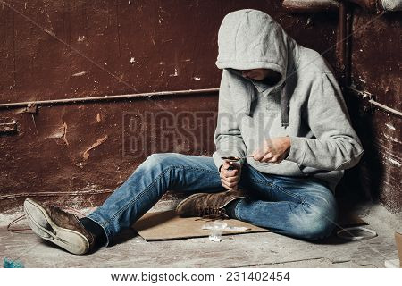 The Hands Of A Drug Addict Melting Cocaine In A Spoon. A Man Holds A Spoon Over A Cigarette Lighter.