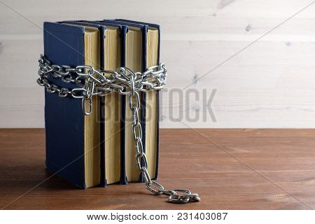 Chain And Book On A Wooden Table Separating A Light And Dark Background A