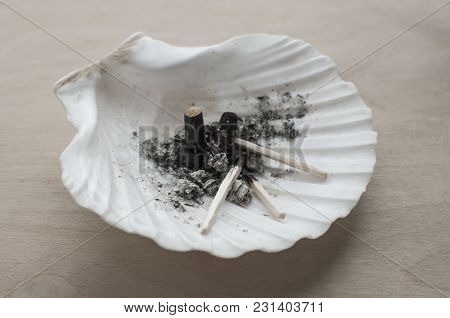 A Sea Shell As Ashtray With Cigarette Butts, Cigarette Ash And Burnt Matches On Wooden Background
