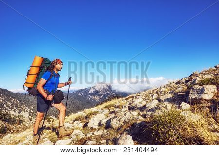 Hiking In The Mountains In The Summer With A Backpack.