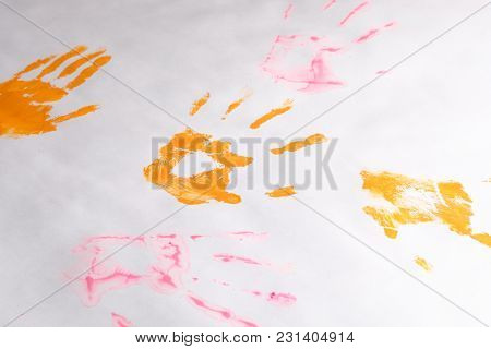 A Little Imprint Of Children's Hands On A White Paper Background, Multi-colored Hands