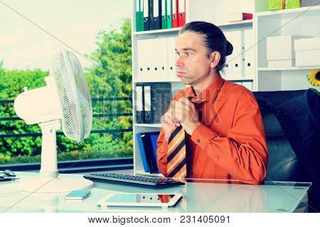 Young Business Man With Ventilator At His Desk In Summerly Hot Office