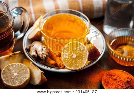 Close Up Of A Herbal Tea  Consisting Of Apple Juice,lemon,ginger And Warm Water In A Transparent Cup