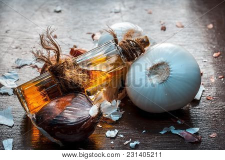 Close Up Of Oil Of Onion Or Allium Cepa L Oil On A Wooden Surface With Raw Onions In Dark Gothic Col