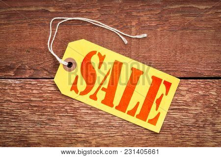 sale sign a yellow paper price tag against rustic red painted wood - shopping concept