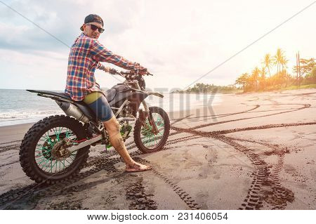 Biker Man With His Sport Motorbike On Black Sand Beach, Enjoying Freedom And Active Lifestyle