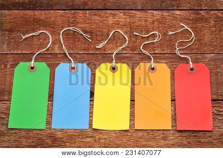 a set of colorful blank paper price tags with a twine against a rustic weathered wood