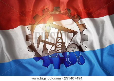 Oil Rig On The Background Of The Flag Of Luxembourg. Mixed Environment. The Concept Of Oil Productio