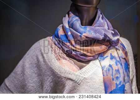 Mannequin With A Patterned Scarf And A Warm Woolen Sweater On A Dark Background