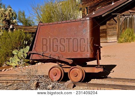 An Old Rusty Mining Handcart Setting On Railroad Tracks For Pushing  Extracted Product Or Supplies