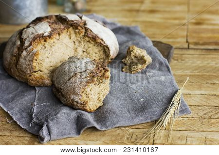 Loaf Of Rye Bread On Grey Napkin On Wooden Table, Rustic Style